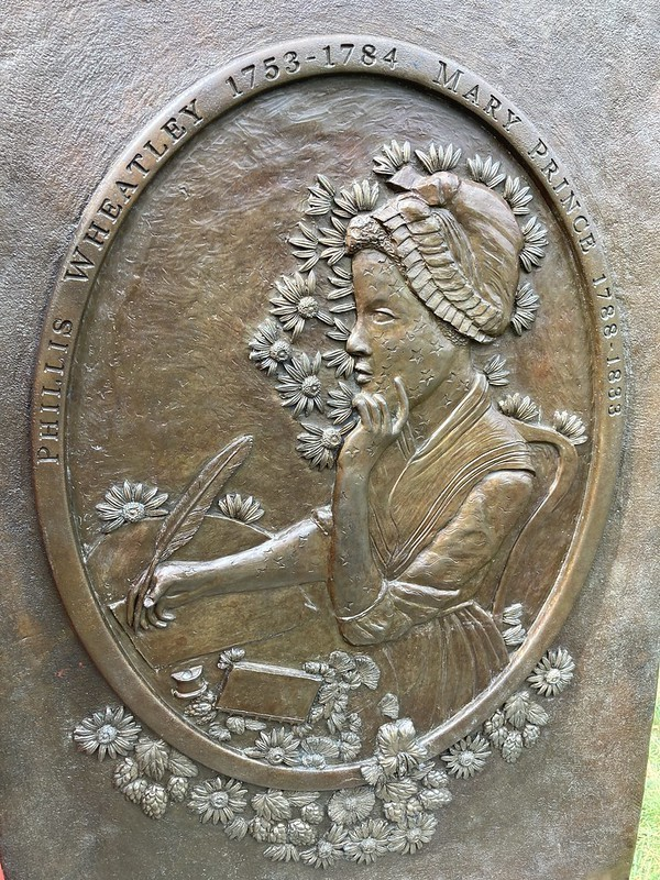 A relief sculpture showing Phillis Wheatley writing with a quill pen.