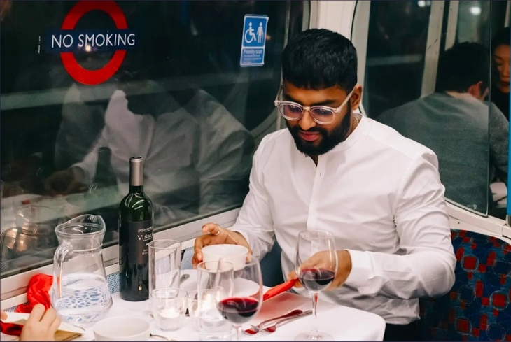 A man tucks into his meal on board a vintage tube carriage