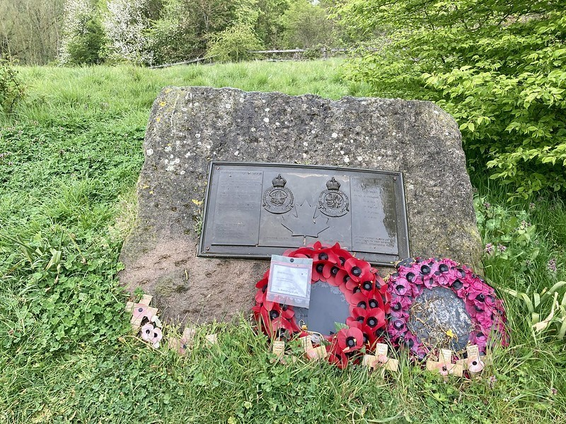 A memorial stone fronted by two poppy wreaths on a background of green grass.