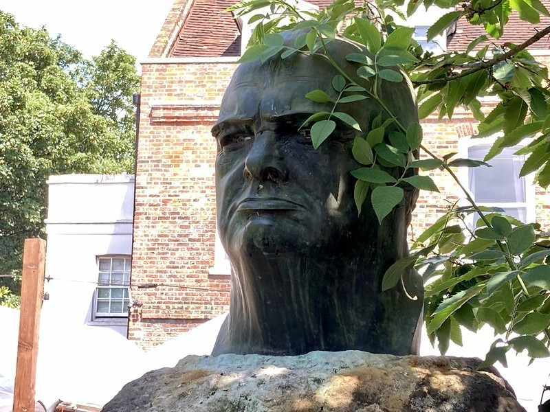 A gurning bust of Winston Churchill perched on top of a granite stone.