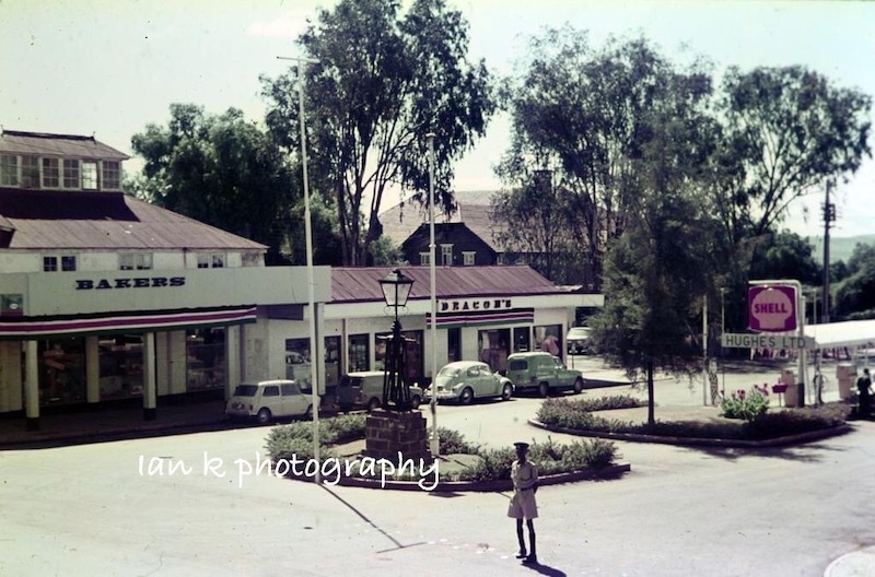 A faded image of a garage in Kenya. At its centre is a lamp post on a granite block.