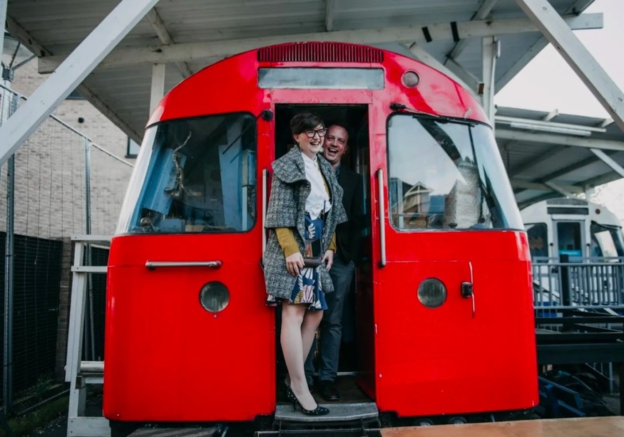 Two people emerge from the front of the tube carriage