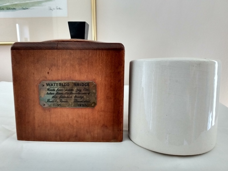 A dark, wooden jar with a plaque giving its origins in the old Waterloo Bridge.