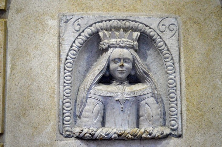 A long-haired stone maiden in a grey stone niche, with the date 1669 across the upper corners.