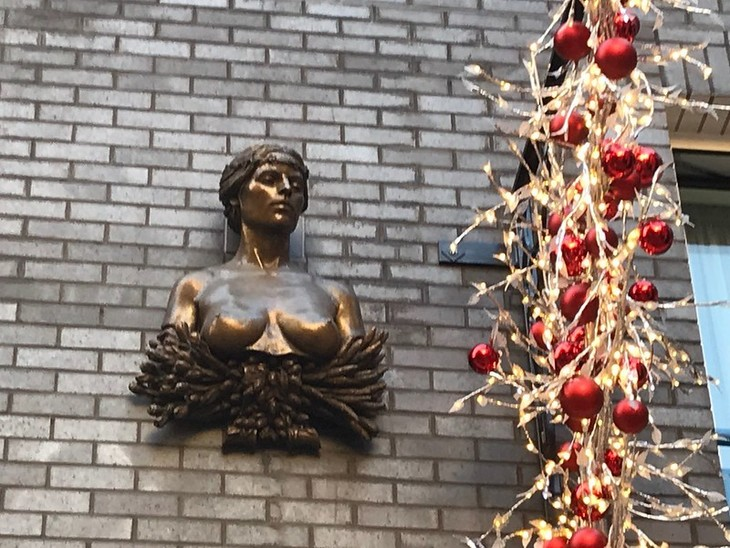 A bust of a maiden with her breasts exposed, alongside a Christmas decoration of gold and red.