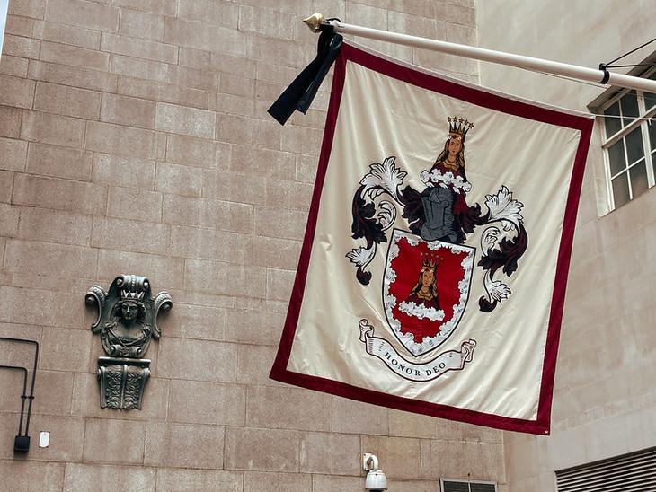 A large flag bearing a red and black coat of arms, is draped before a stone wall bearing a small mercers maiden.