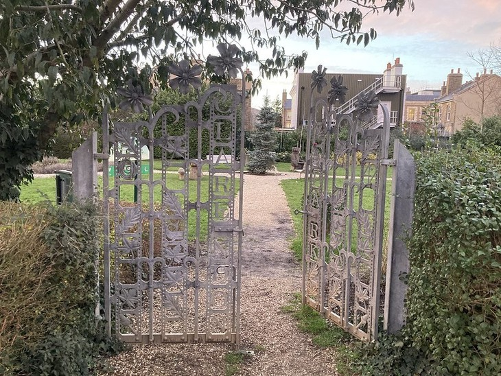 An open gateway (large wrought iron gates) leading into a park.