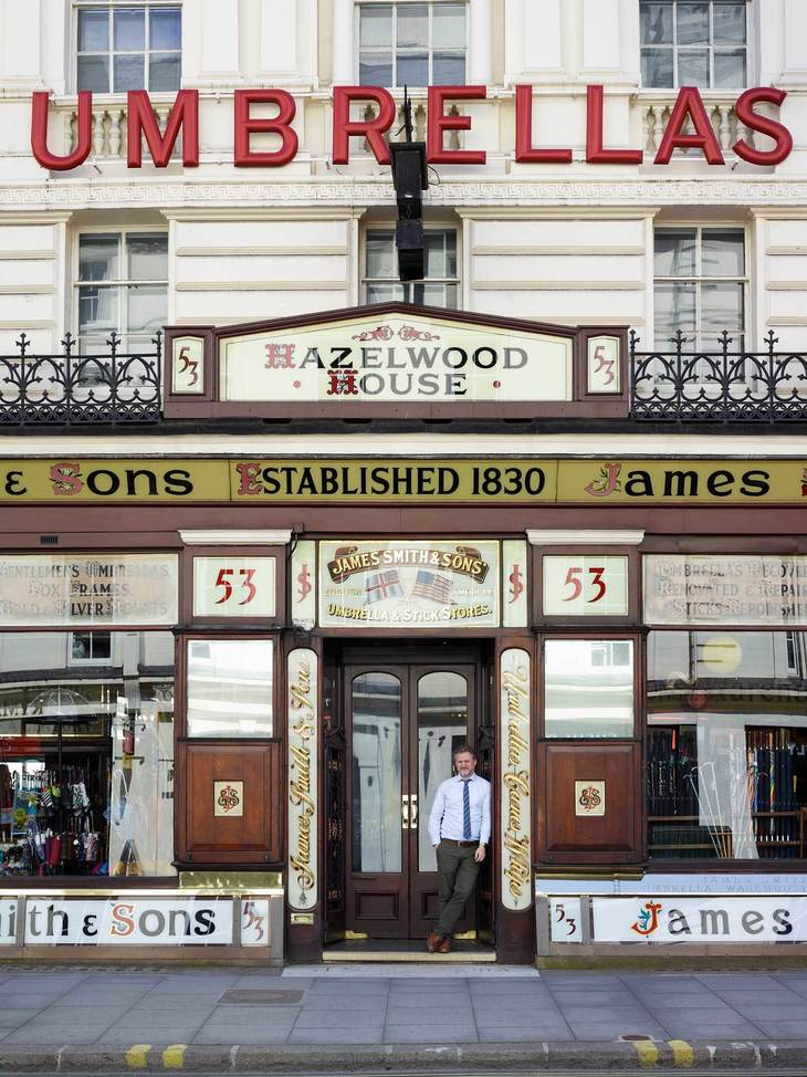 store manager Philip Naisbitt  stands out side the famous umbrella shop