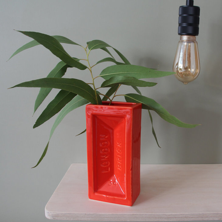 A bright orange vase in the shape of a london brick