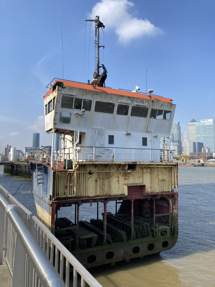 the slice up ship, backdrop by the skyscrapers of canary wharf