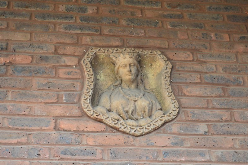A maiden gazes out from a balcony. The background is red brick.