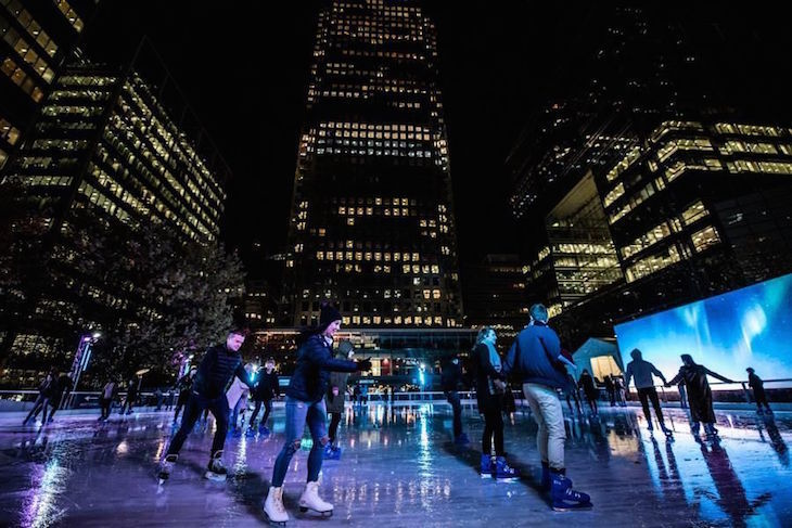People skating on an ice rink in the dark, with skyscrapers in the background, illuminated by lights in the windows