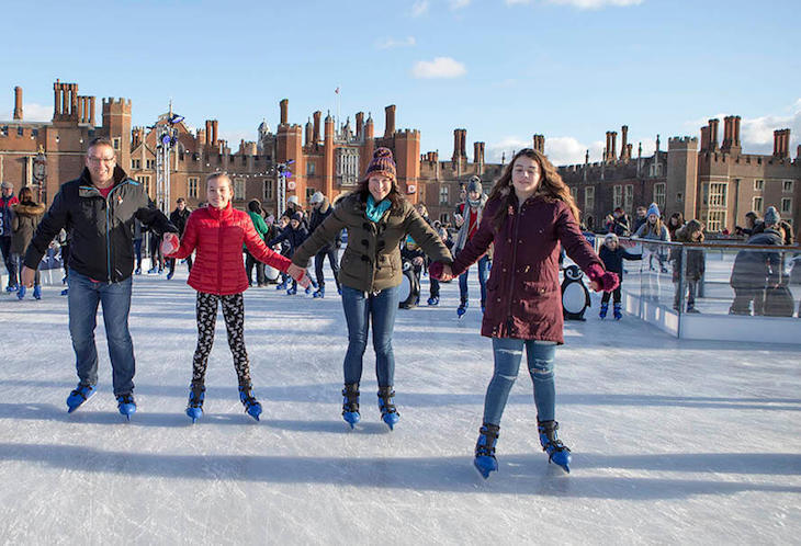 Four ice skaters hold hands while skating on an ice rink in front of Hampton Court Palace in daylight