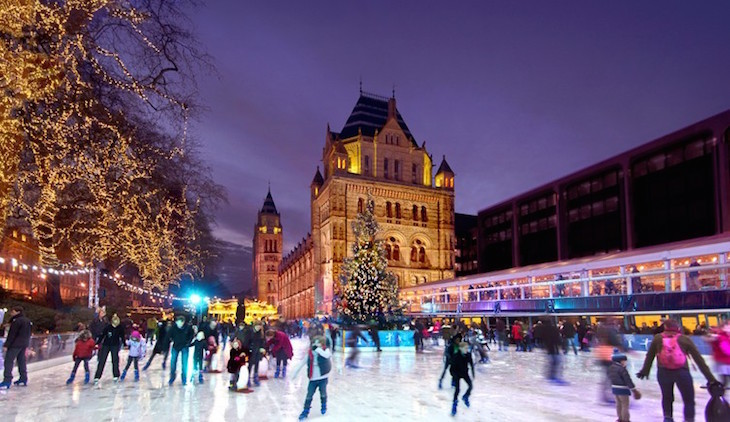 People ice skating around a large Christmas tree in front of the Natural History Museum