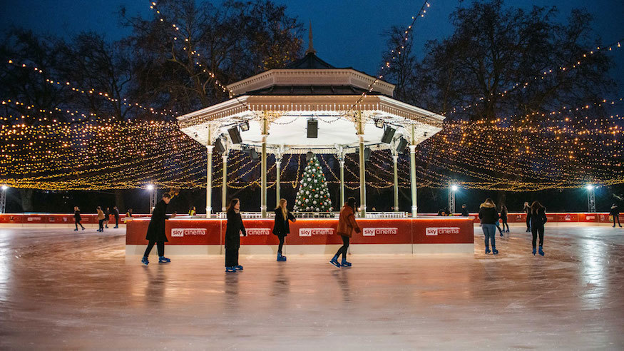 A Victorian bandstand in the centre of an ice rink at dusk. A few people are on the ice, with fairy lights strung overhead, and a decorated Christmas tree inside the bandstand.