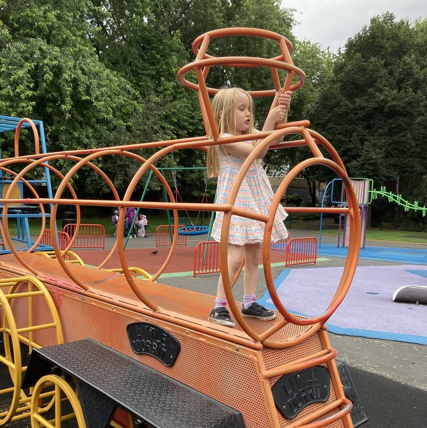 A girl climbs on an orange wireframe train in a playground.
