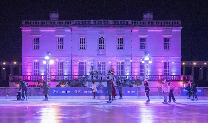 Queen's House Greenwich facade, with an ice rink in front of it at night, both illuminated purple, with skaters on the ice