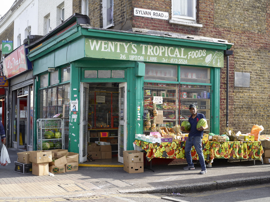 wenty holds melons outside his fruit shop